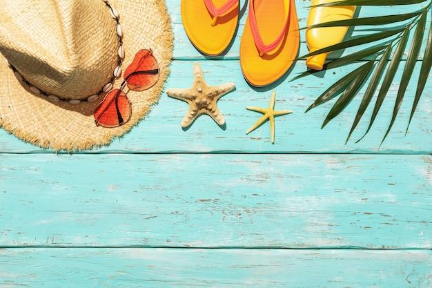 Kapeluszowe okulary przeciwsłoneczne kapcie plażowe z filtrem przeciwsłonecznym i rozgwiazda z liściem palmowym na niebieskim drewnianym tle z letnim tłem przestrzeni kopii