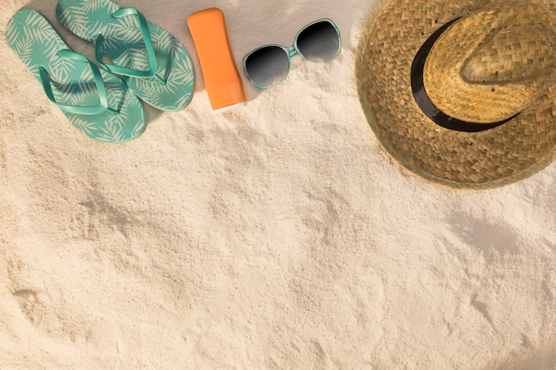 Kapeluszowe okulary przeciwsłoneczne niebieskie sandały i krem przeciwsłoneczny na piasku