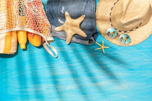 Kapeluszowe szorty przeciwsłoneczne i inne akcesoria plażowe na niebieskim drewnianym tle z miejscem na kopię