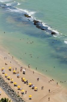 Kąpiący się na plaży boa viagem i kolorowe parasole recife pernambuco brazylia 27 września 2008 r.