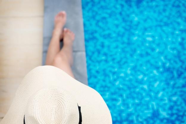 Kąpiele słoneczne kobiety na basenie pływają w pobliżu morza i plaży w zachodzie słońca