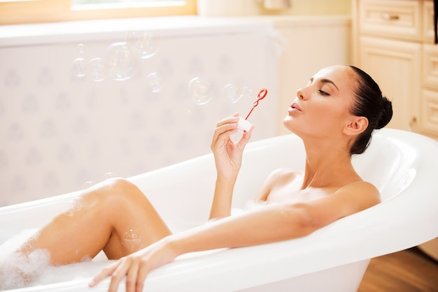 Kąpieli. widok z boku pięknej młodej kobiety dmuchającej bańki mydlane podczas kąpieli z bąbelkami