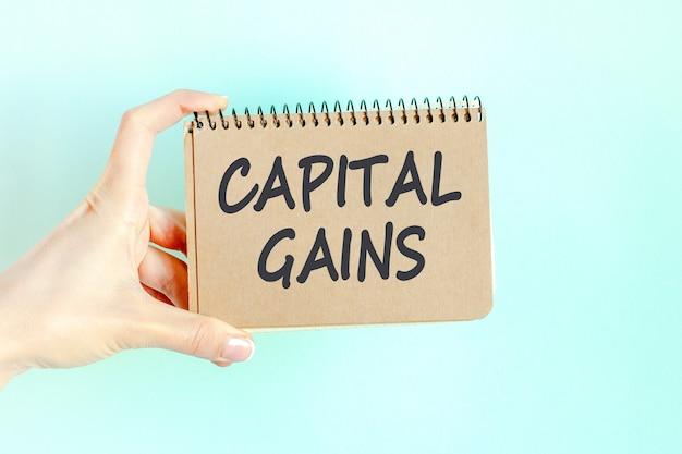 Kapitał zyskuje napis słowo na kartce papieru w rękach bizneswoman