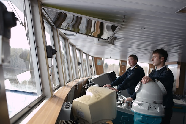 Kapitan jedzie statkiem po rzece.