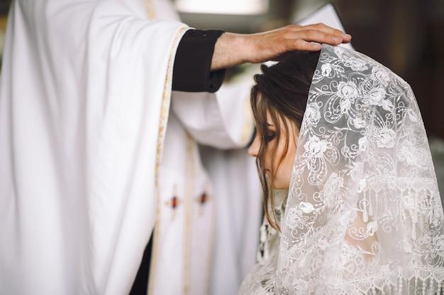 Kapłan błogosławi oblubienicę podczas ceremonii w kościele