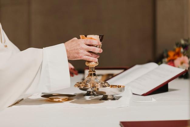Kapłan trzymający kielich podczas mszy weselnej. koncepcja religii