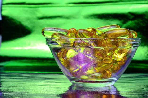 Kapsułka omega 3. w szklanej misce na kolorowym tle.
