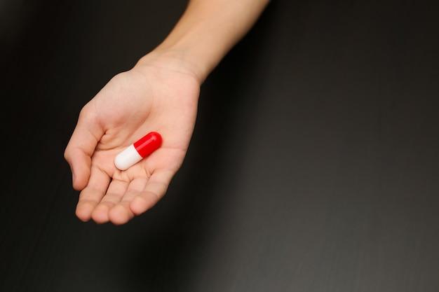 Kapsułka tabletki leku znieczulającego leży w dłoni młodego mężczyzny