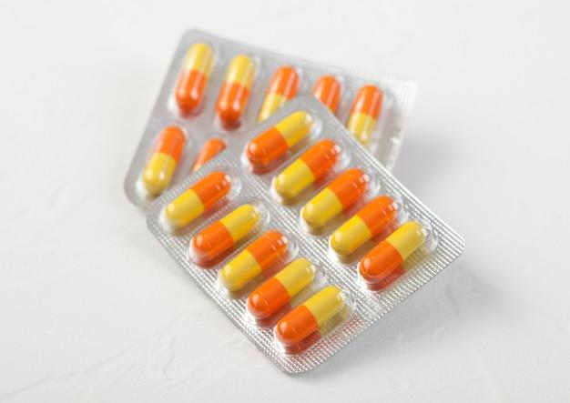Kapsułka tabletki w plastikowym pasku na białym tle. antybiotyki, witaminy, środek przeciwbólowy.