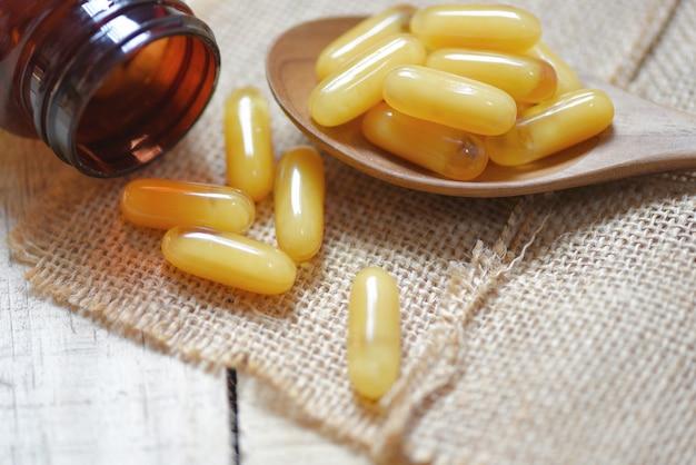 Kapsułki galaretki królewskiej w drewnianą łyżką i worek - żółta kapsułka medycyny lub uzupełniające jedzenie z natury dla zdrowia