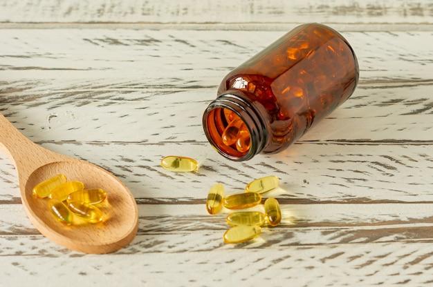 Kapsułki oleju rybnego na drewniane tła i tekstury, witamina d, suplement omega, selektywne focus.
