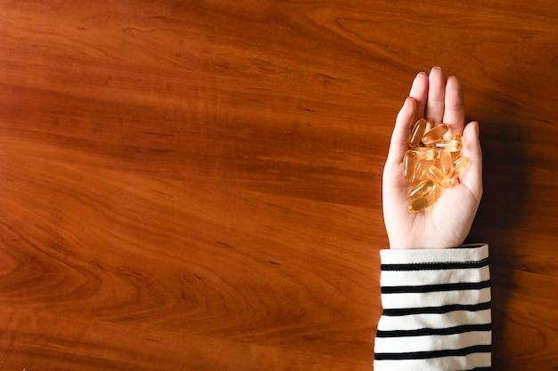 Kapsułki oleju rybnego w dłoni