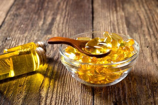 Kapsułki oleju z ryb na podłoże drewniane