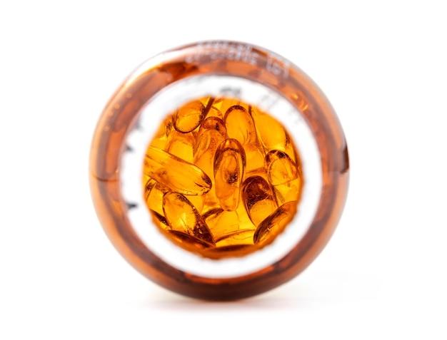 Kapsułki uzupełniające olej rybny wewnątrz otwartego opakowania butelki z brązowego szkła na białym tle