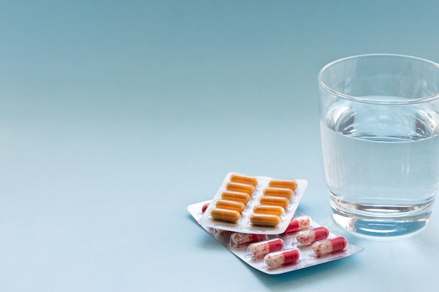Kapsułki w blistrze z wodą w przezroczystym szklanym kubku na niebieskiej powierzchni koncepcja medycyny