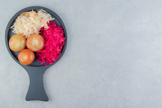 Kapusta kiszona i marynowane pomidory na czarnej tablicy.