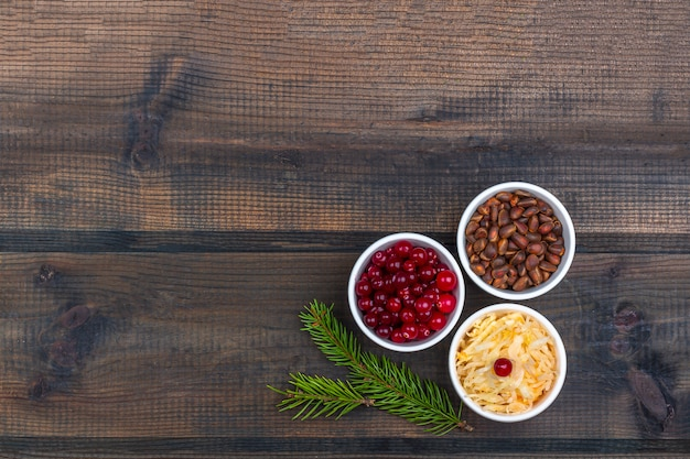 Kapusta kiszona lub sfermentowana kapusta z żurawiną i orzeszkami piniowymi na rustykalne drewniane tła. pojęcie zdrowego odżywiania. żywność ekologiczna i wegetariańska, składniki fermentacyjne. ścieśniać