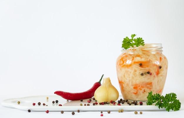 Kapusta kiszona lub sfermentowana marchewka z białej kapusty z przyprawami i ziołami. otwórz szklany słoik z merinowanych warzyw