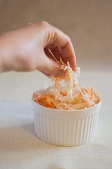 Kapusta kiszona w białej ceramicznej misce. domowa kapusta kiszona z marchewką. sfermentowane jedzenie.
