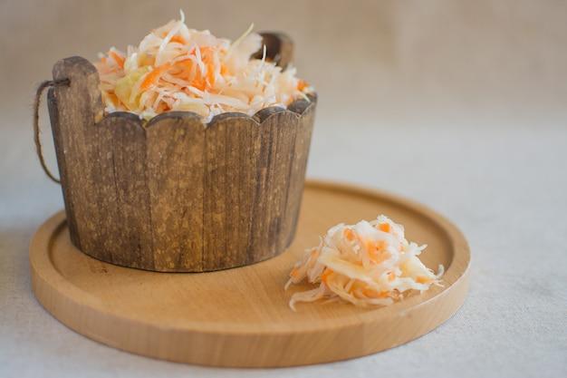 Kapusta kiszona w drewnianej beczce na okrągłym drewnianym stojaku. domowa kapusta kiszona z marchewką. sfermentowane jedzenie.