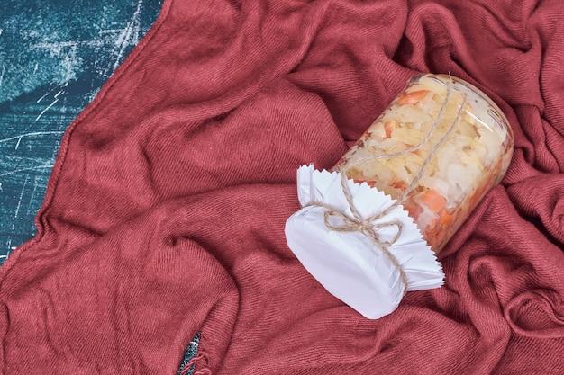 Kapusta kiszona w szklanym słoju na niebiesko z czerwonym obrusem.