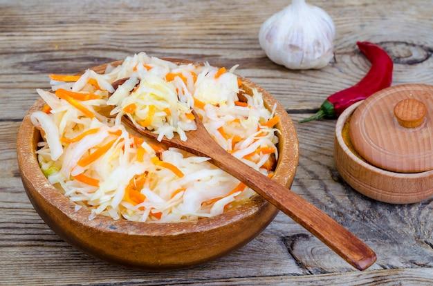 Kapusta kiszona z marchewką w drewnianej misce na stole