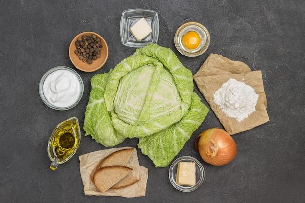 Kapusta włoska, mąka na papierze, rozbite jajko w szklanej misce, oliwa, cebula i kromki chleba. czarne tło. płaskie ułożenie