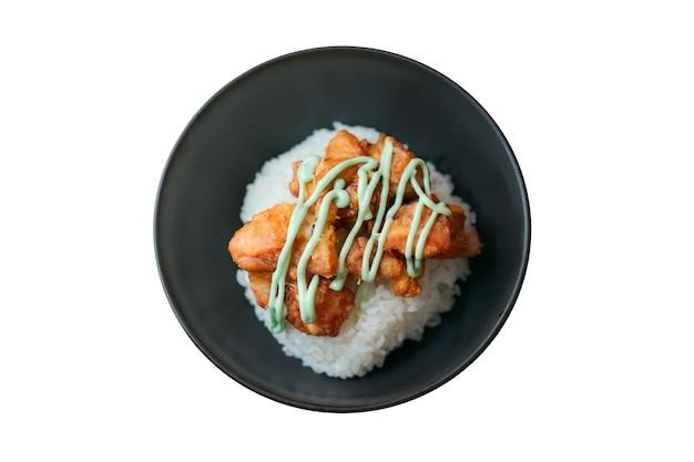 Kara-age wasabi gotowa (smażony kurczak z sosem wasabi na ryżu) w czarnej misce jest izolowana i widok z góry.