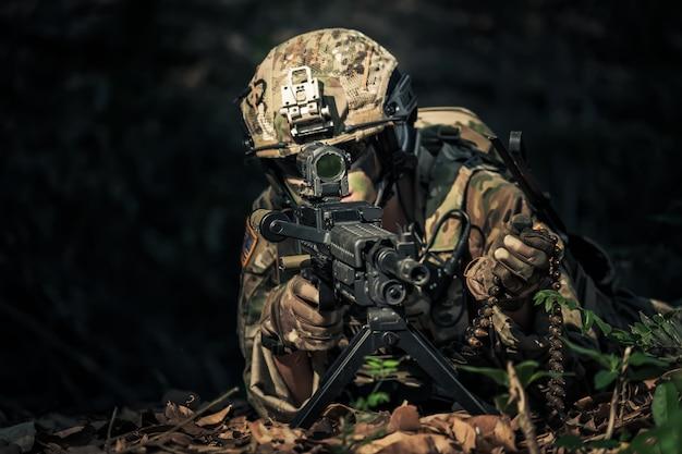 Karabin szturmowy żołnierza sił specjalnych z tłumikiem. snajper w lesie.