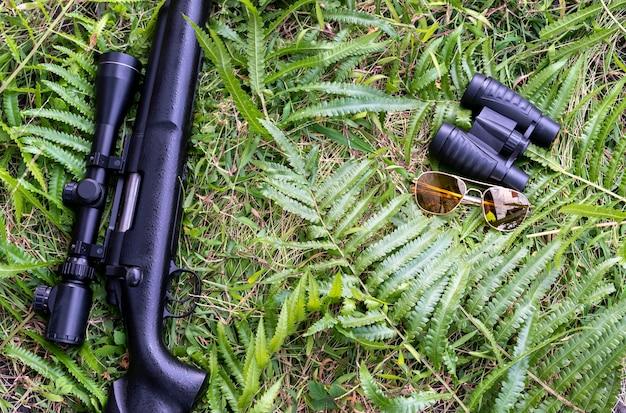 Karabiny i lornetki na trawiastej podłodze