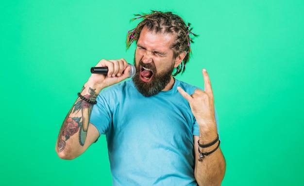 Karaoke. brodaty mężczyzna śpiewa z mikrofonem. nagrania studyjne.