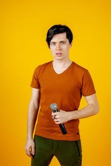 Karaoke mężczyzna śpiewa piosenkę do mikrofonu, na żółtym tle. zabawny człowiek trzyma mikrofon w dłoni przy śpiewaczce karaoke śpiewającej piosenkę! pity na żółtym tle