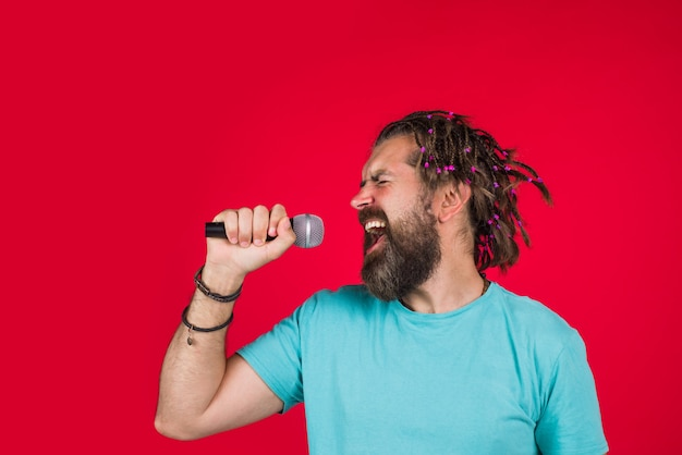 Karaoke. mężczyzna śpiewa z mikrofonem. nagrania studyjne. brodaty mężczyzna śpiewa w mikrofonie. mikrofon. zaśpiewaj piosenkę. śpiew w studio.