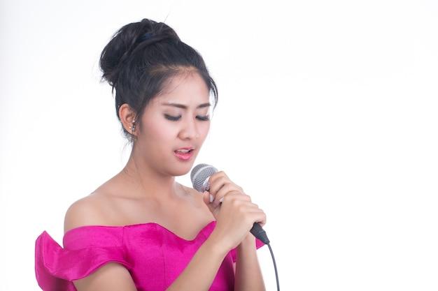 Karaoke, młoda dziewczyna trzyma mikrofon do śpiewania i radości przy jej muzyce na białym tle.