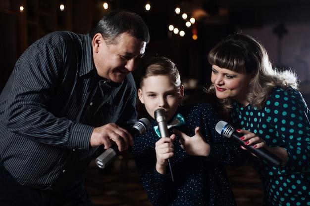 Karaoke rodzinne. portret szczęśliwej rodziny, śpiewa w mikrofonach