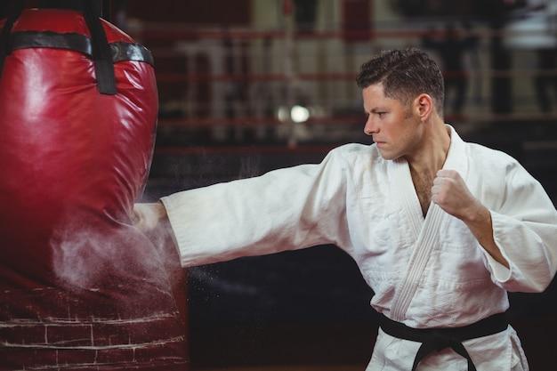 Karate gracz ćwiczy karate z workiem treningowym