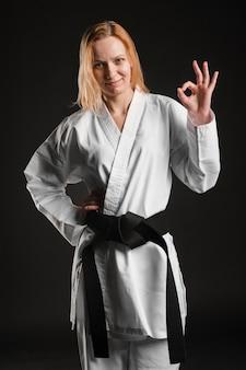 Karate kobieta pokazuje ok znaka