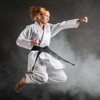 Karate kobieta skacze pełny strzał