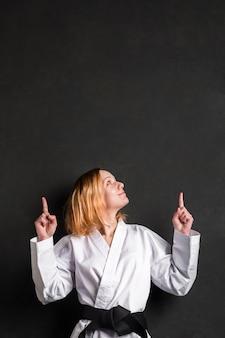 Karate kobieta wskazuje przy kopii przestrzenią