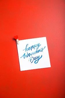 Karciana wiadomość z szczęśliwym kobieta dniem na czerwień stole