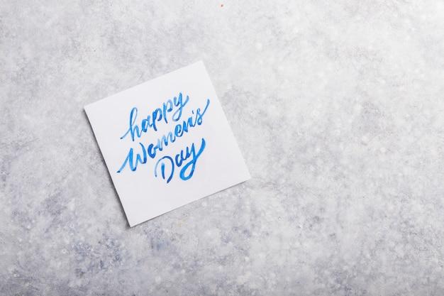 Karciana wiadomość z szczęśliwym kobieta dniem na popielatym stole