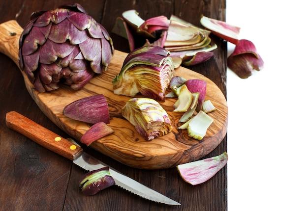 Karczochy rzymskie na drewnianej desce z nożem
