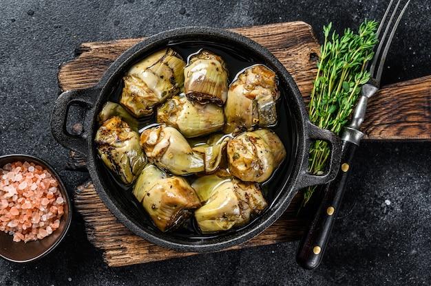 Karczochy w puszce w oliwie z oliwek na rustykalnym drewnianym stole kuchennym. widok z góry.