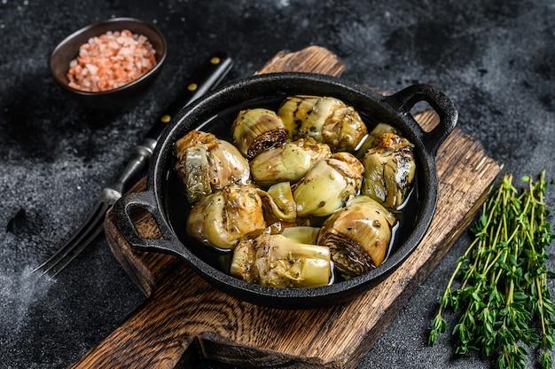Karczochy w puszce w oliwie z oliwek na rustykalnym drewnianym stole kuchennym.