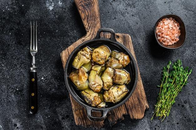 Karczochy w puszkach w oliwie z oliwek na rustykalnym drewnianym stole kuchennym. czarne tło. widok z góry.