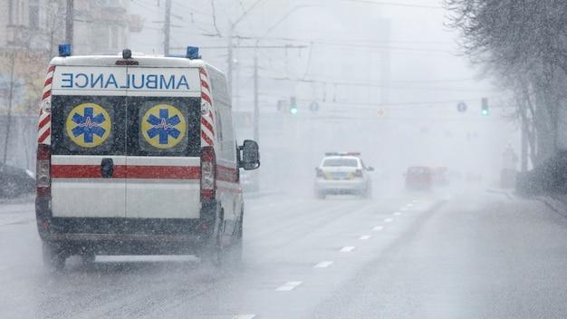 Karetka zabrała pacjenta do kliniki z włączonymi kierunkowskazami. zła pogoda na zewnątrz, deszcz z mokrym śniegiem.