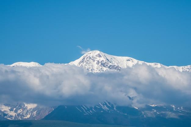 Karkonosze ze śniegiem nad białymi chmurami w słoneczny dzień. lodowiec pod błękitnym niebem. niesamowity śnieżny krajobraz górski o majestatycznej przyrodzie.