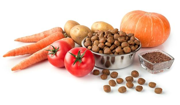 Karma dla psów lub kotów na naczyniu ze stali nierdzewnej z surowymi warzywami na białym tle do projektowania o sklepie zoologicznym.