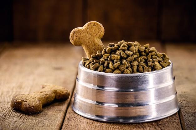 Karma dla psów z herbatnikiem w kształcie kości w metalowej misce na drewnianym tle, kopia przestrzeń
