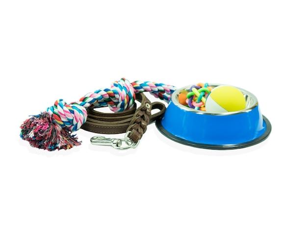 Karma dla zwierząt domowych ustawiona wokół miski ze stali nierdzewnej, liny, gumowych zabawek i skóry ze smyczy dla psa